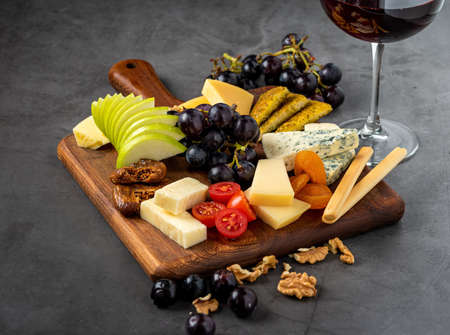 Red Wine And Assorted Cheese Plate with fruit on wooden plate