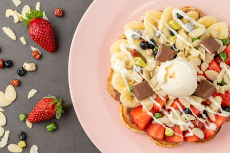 Heart waffle with banana and strawberry with gummy candy and ice cream on it. 免版税图像