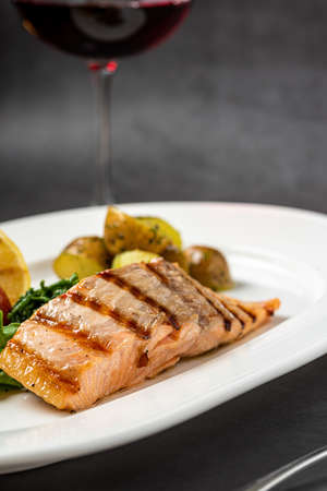 Grilled salmon fillet with vegetables mix. dark background