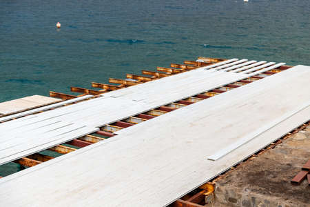 The pier where white composite deck is installed by the sea. 免版税图像