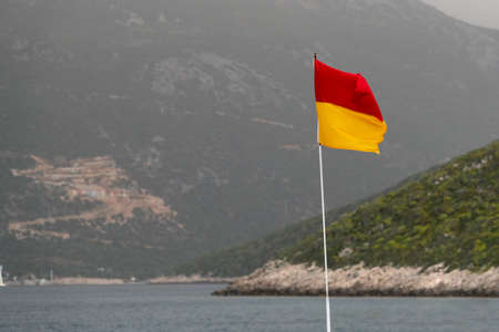 A red and yellow life saving flag by the sea.
