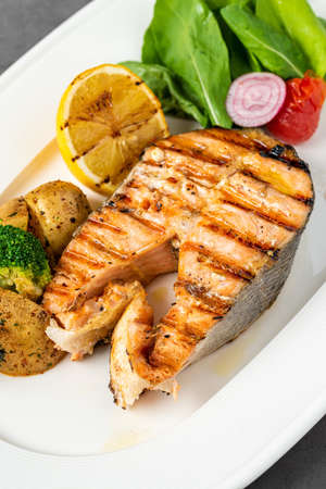 plate of grilled salmon steak with vegetables on dark stone table