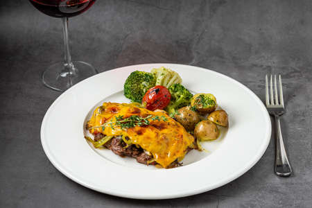 Cheddar cheese beefsteak with potatoes and broccoli on dark stone background 免版税图像