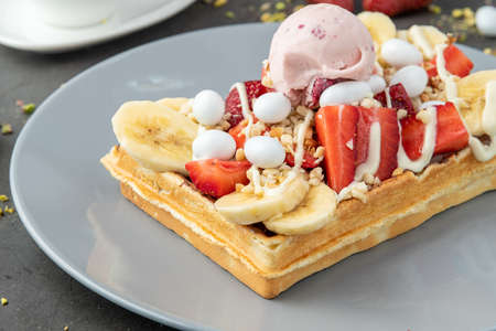 belgium waffles with strawberry and banana on stone background 免版税图像