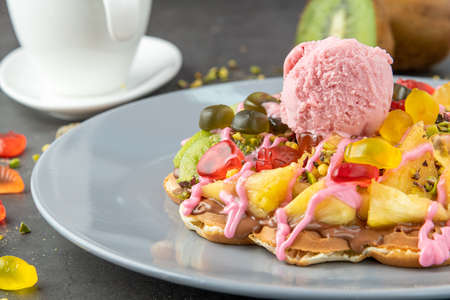 Heart waffle with kiwi and pineapple with gummy candy and ice cream on it.