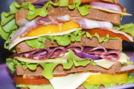Huge high biggest sandwich with pork beef cheese salad tomato and vegetables burger on a violet plate black background