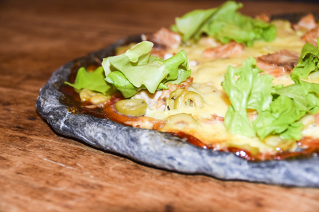 Black  Dough Pizza With Salmon on wooden background