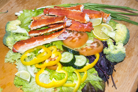 Legs of the claws of the king crab dish of vegetables broccoli onion pepper cucumbers tomato mushrooms salad