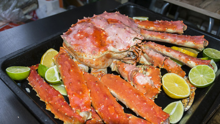 Royal crab in a baking sheet with lemon lime on a black background