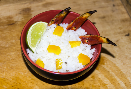 A bowl of rice with crab lime pineapple pepper on a wooden background Stock Photo