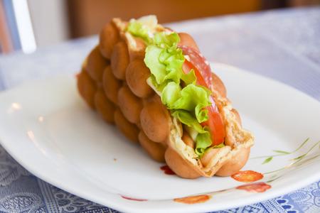 Hong Kong bubble waffle with salami cheese and tomato salad Stock Photo