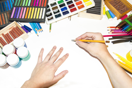 The artist`s hands  start of work  workplace  workshop art materials white list Stock Photo