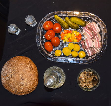 Tsarist still life luxury decanter of vodka and appetizer lard pickled cucumbers tomatoes pepper mushrooms black bread on a black background crumbs