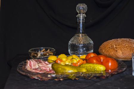 Tsarist still life luxury decanter of vodka and appetizer lard pickled cucumbers tomatoes pepper mushrooms black bread on a black background crumbs Standard-Bild