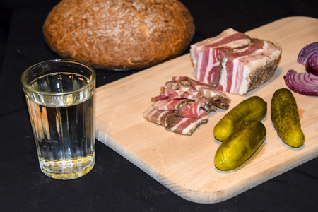 still life glass of russian vodka and snack lard bream pickled cucumbers onion garlic bread on a wooden board on a black background