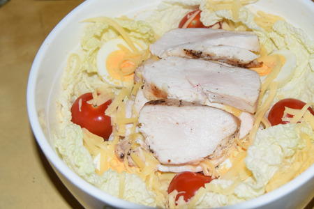 homemade caesar salad in a large bowl abstract background chicken cheese tomatoes