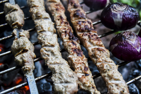 BBQ on the nature in summer meat kebab grilled over charcoal red onions on  grill