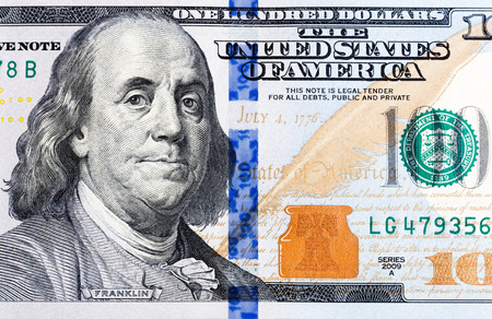 Macro shot of a brand new one hundred dollar bill showing the face of Benjamin Franklin.