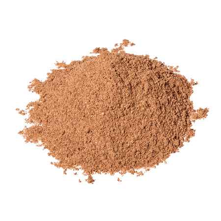 Pile of Nutmeg powder isolated on white background. Used as a spice in many sweet as well as savoury dishes and medicine.