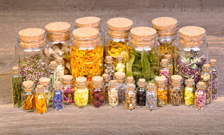 Healing herbs in bottles for herbal medicine on old wooden table.