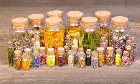 mortero: Hierbas curativas en botellas de la medicina a base de hierbas en la mesa de madera vieja. Foto de archivo