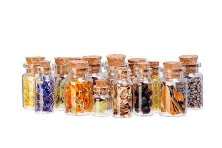 valerian plant: Herbal tea dried herbs flowers and berries in glass bottles for medical use on white background.