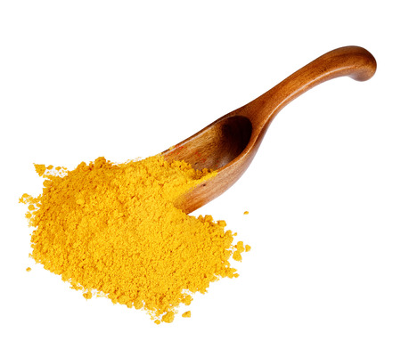 spoon yellow: Yellow curry powder in the wooden spoon, isolated on white background.