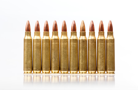 m16 ammo: Rifle bullets in a row isolated on white background. Stock Photo