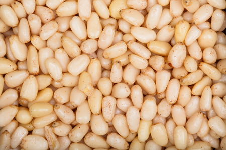 pinaceae: Background texture of shelled pine nuts. Stock Photo