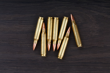 full jacket bullet: Old ammunition on the wood background. Army equipment.