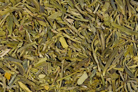 theine: Long leaves green loose tea (Dragon well), macro photo, texture.