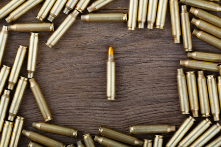 m16 ammo: M-16 bullet on wooden table close-up.