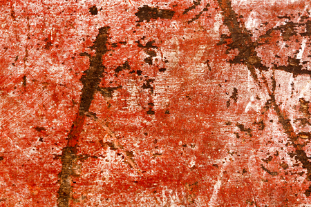 heavily: Heavily damaged scratched piece of red painted wood. Stock Photo