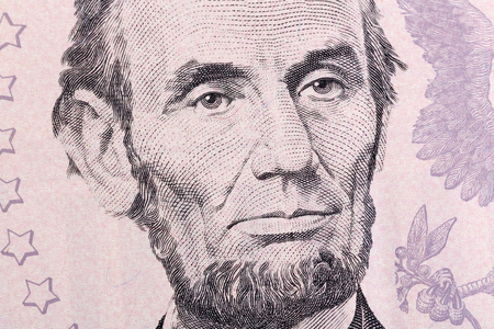 five dollar bill: Macro portrait of Abraham Lincoln on five U.S. dollar bill.