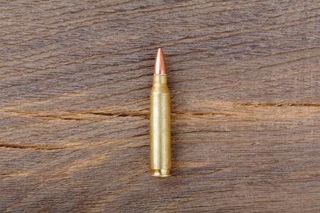 m16 ammo: Rifle bulet on old wood desk.