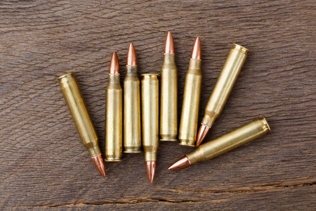 sportsmanship: Bullets on rustic wooden background. Stock Photo