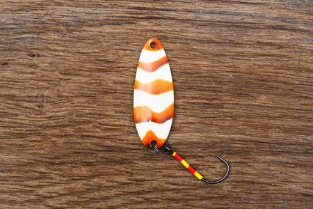 color image fish hook: Bait for trout fishing on the old wooden table. Stock Photo