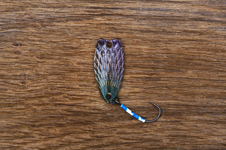 color image fish hook: Fishing lure for trout fishing on the old wooden table. Stock Photo