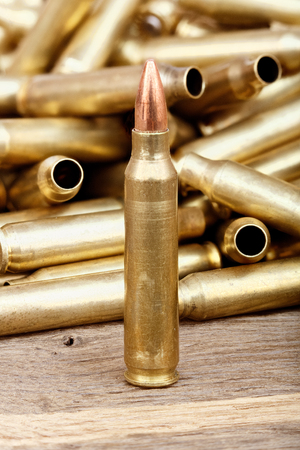 full jacket bullet: Close-up photo of bullet on the wooden table.