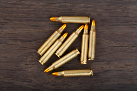 shootings: Fire arm bullet cartridges on a old wooden floor.