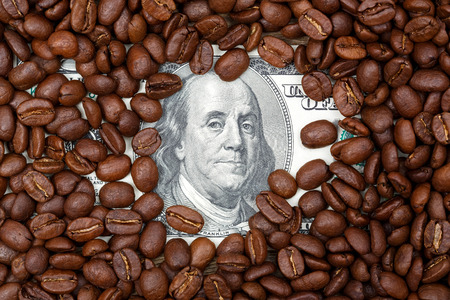 Dollars (US money) covered with coffee beans.
