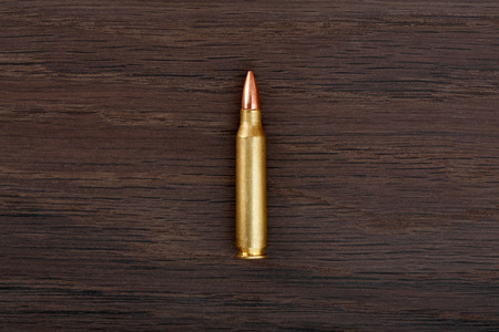 shootings: Single rifle bullet on old wooden table.