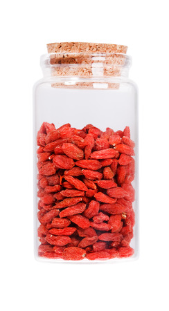 stopper: Dried goji berries in a glass bottle with cork stopper, isolated on white.