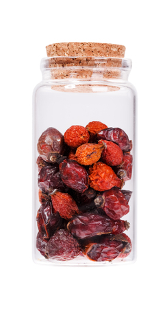 stopper: Berries dried rosehips in a glass bottle with cork stopper, isolated on white. Stock Photo
