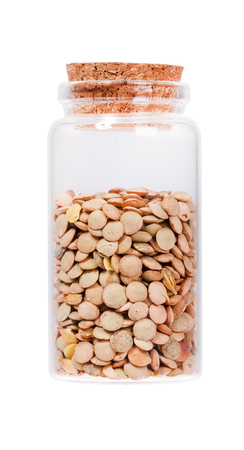 stopper: Lentils in a glass bottle with cork stopper, isolated on white. Stock Photo