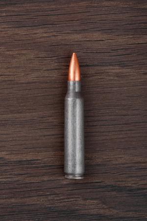 ak47: Ak-47 bulet on old wooden surface.