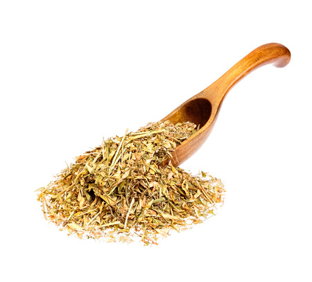herba: Capsella bursa-pastoris on a wooden spoon isolated on white.