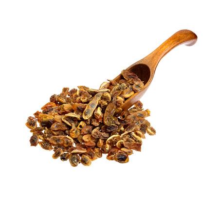 Dried sophora japonica beans on the wooden spoon. Reklamní fotografie