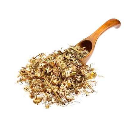 herbolaria: Té de manzanilla a base de hierbas en la cuchara de madera.