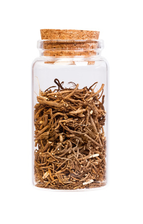 valerian: Valerian root in a bottle with cork for medical use.